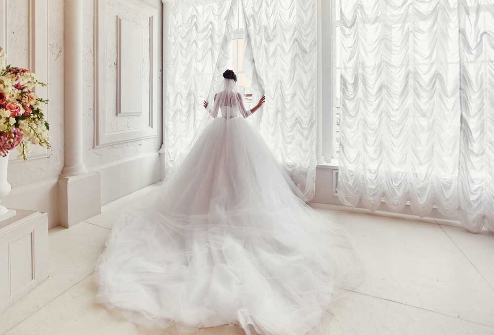 A woman wearing a wedding dress in a large house